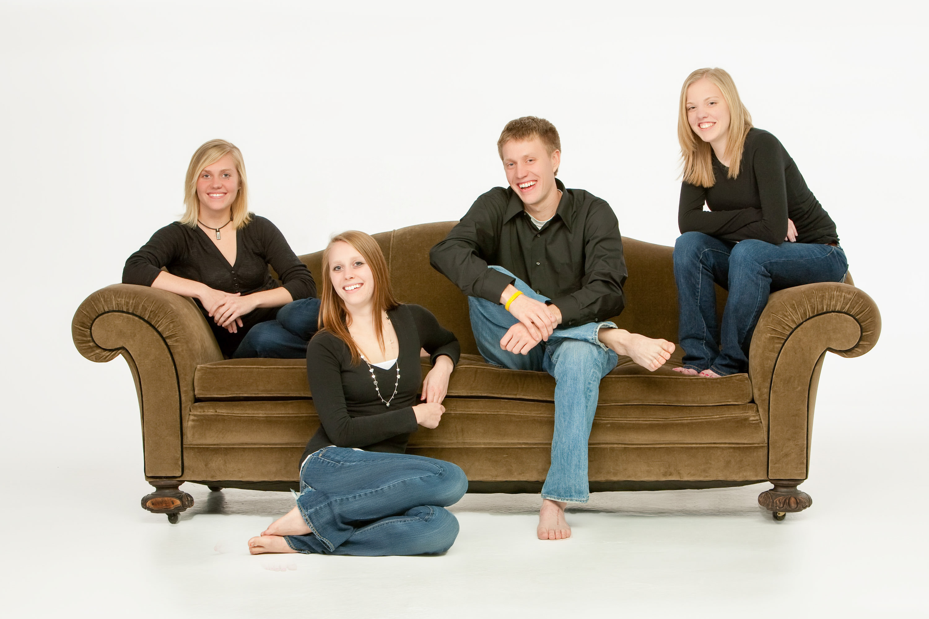 Family of 4 brothers and sisters in a casual, contemporary modern arrangement on a couch.